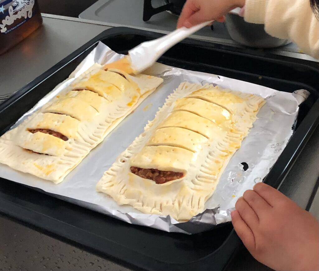 ミートパイに卵黄を塗る様子